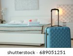 Stock photo blue suitcase in light hotel room 689051251
