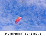 Small photo of Paramotor wing airman and motorless flying with a glider against blue sky. Focus so desired