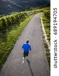 jogger on a road in a vineyard... | Shutterstock . vector #689194705