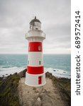 a red and white lighthouse in... | Shutterstock . vector #689572414