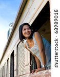Small photo of Girl in a train window. Old train at Phnom Penh railway station with a pretty Khmer girl smiling and looking out from the train window. Girl wearing retro style ageless clothes. Vintage feeling.