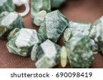 Small photo of Macro shot of serpentine crystals in necklace. Natural, beautiful gemstones. Serpentine stone has a strong energy known to stimulate the arousal of the kundalini energies