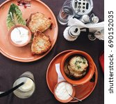 Small photo of Delicious belarussian Draniki with sour cream ion the table, flat lay