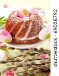 traditional ring cake with icing sugar on easter table decorated with catkins - stock photo