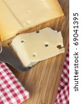Block of cheese with cheese slicer and slice of cheese on cutting board. - stock photo