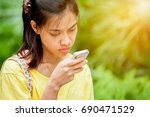 asian girl playing phone... | Shutterstock . vector #690471529