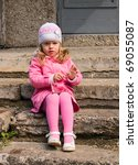 Little girl sits on a stone staircase - stock photo