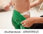 mom takes off his pants the kid ... | Shutterstock . vector #690559015