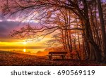 Stock photo romantic autumn mood at sunset at lake ammersee in bavaria an empty park bench at the edge of the 690569119