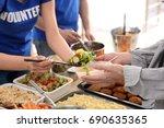 volunteers giving food to poor... | Shutterstock . vector #690635365
