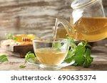 pouring aromatic lemon balm tea ... | Shutterstock . vector #690635374