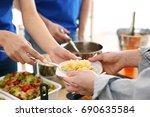 volunteers giving food to poor... | Shutterstock . vector #690635584