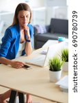 woman sitting on the desk with... | Shutterstock . vector #690780739