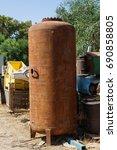 Small photo of Rusty air pressure vessel dumped in the junkyard.
