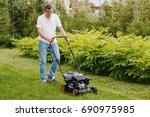 a young man mows the lawn | Shutterstock . vector #690975985