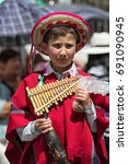 Small photo of June 17, 2017 Pujili, Ecuador: young boy in traditional clothing at the Corpus Christi parade holding a pan flute