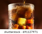 pouring cola with ice cubes.... | Shutterstock . vector #691127971