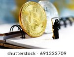 Small photo of Miniature: Demon of death standing with bitcoin. Financial and business concept.