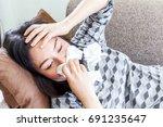 sick woman blowing her nose... | Shutterstock . vector #691235647