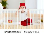 funny baby bites his cot as... | Shutterstock . vector #691297411