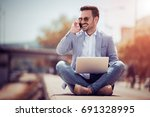 handsome young man using laptop ... | Shutterstock . vector #691328995