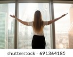 Small photo of Confident businesswoman spreading hands standing at office window, enjoying big city, successful entrepreneur celebrating business success with arms open wide, feeling powerful inspired, rear view
