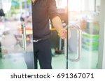 man's hand open the door with... | Shutterstock . vector #691367071
