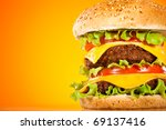 Tasty and appetizing hamburger on a yellow background - stock photo