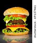 Tasty and appetizing hamburger on a dark background - stock photo