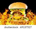 Tasty hamburger on fire on a dark background - stock photo