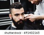 master cuts hair and beard of... | Shutterstock . vector #691402165