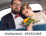 young newlywed couple sitting... | Shutterstock . vector #691411465