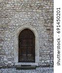 ancient door in a stone wall | Shutterstock . vector #691450201