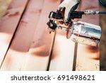male worker using spray gun for ... | Shutterstock . vector #691498621