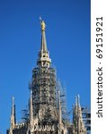 The Duomo, gothic cathedral of Milan, roof with pinnacles and holy Mary golden statue, Lombardy, Italy - stock photo
