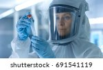 Small photo of Medical Virology Research Scientist Works in a Hazmat Suit with Mask, Inspects Test Tube with Isolated Virus String from Refrigerator Box. She Works in a Sterile High Tech Laboratory Facility.