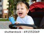 little boy is sitting in a pram ... | Shutterstock . vector #691552069