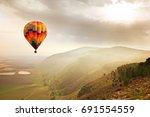 a hot air balloon in the mist... | Shutterstock . vector #691554559