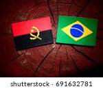 Small photo of Angolan flag with Brazilian flag on a tree stump isolated