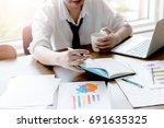 businessman sitting on the desk   Shutterstock . vector #691635325