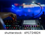 Sound technician and lights technicians control the music show in concert.Professional audio,light mixer controller panel.Pro equipment for concerts.Stage lighting control.Hand adjusting audio mixer - stock photo