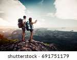 Two Hikers Relax On Top Of A...