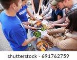 volunteers sharing food with... | Shutterstock . vector #691762759