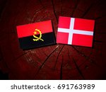 Small photo of Angolan flag with Danish flag on a tree stump isolated