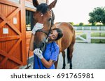 Stock photo vet kissing a horse outdoors at ranch 691765981
