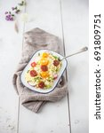Small photo of Vegan Tabbouleh salad, Arabic food made of bulgur wheat on a wooden portrait background with flowers, linen fabric and a spoon