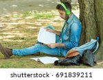 college student studying in park | Shutterstock . vector #691839211