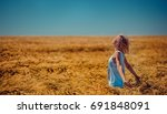 Small photo of Girl standing at the wheat field against the wind