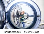 boy puts clothes in a washing... | Shutterstock . vector #691918135