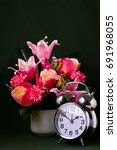 a silver alarm clock and a vase ...   Shutterstock . vector #691968055